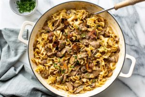 Overhead view of a casserole pan filled with sliced beef, egg noodles, mushrooms in a rich gravy
