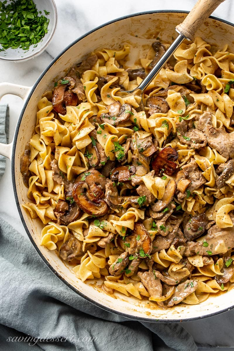A skillet filled with beef, noodles and mushrooms in a creamy sauce