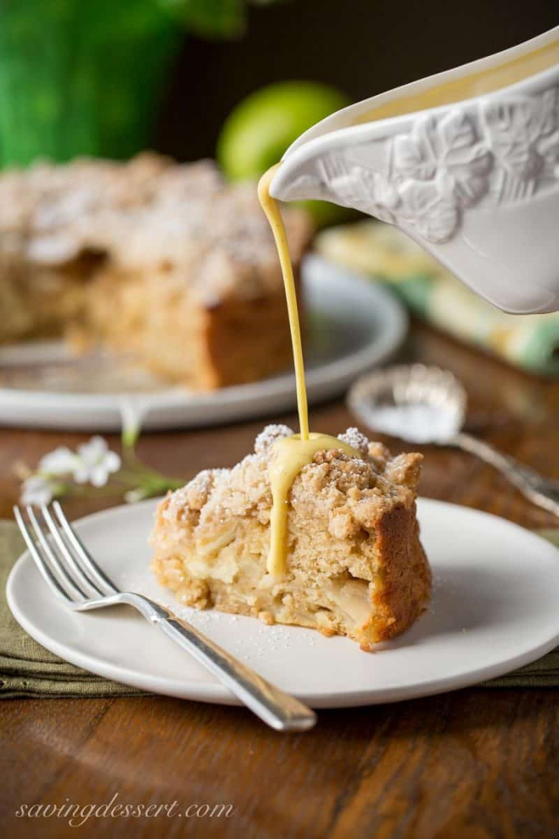 A slice of apple cake drizzled with a creamy sauce