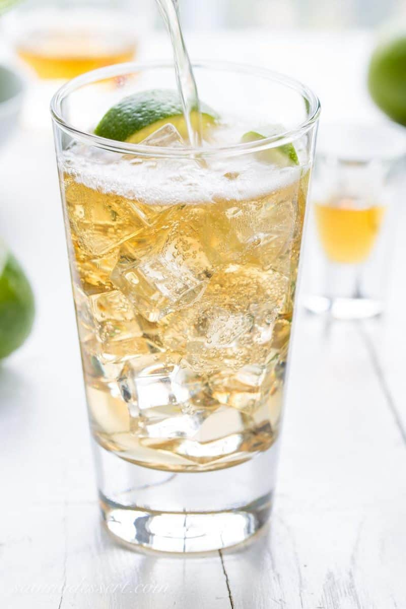 A glass of Jameson Irish Whiskey poured over ice with ginger ale and lime wedges