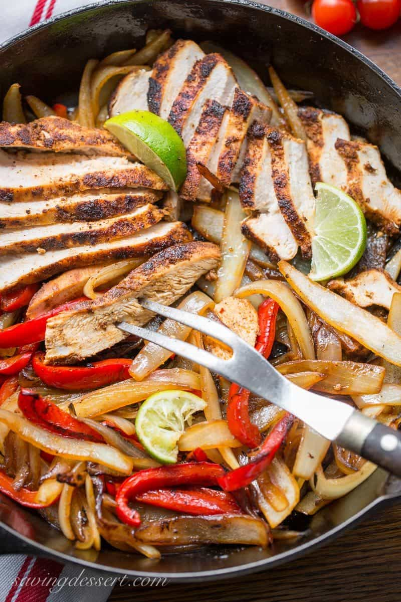 A skillet with peppers, onions and chicken for Skillet Fajitas