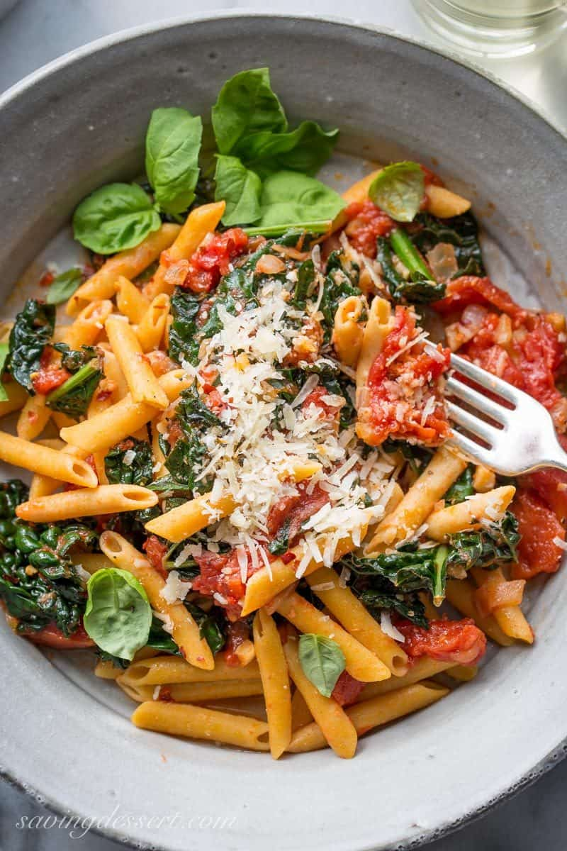 A bowl of kale, tomatoes and pasta with fresh grated Parmesan and basil leaves