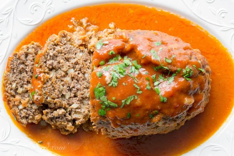 Sliced Dutch meatloaf with a rich tomato sauce and parsley