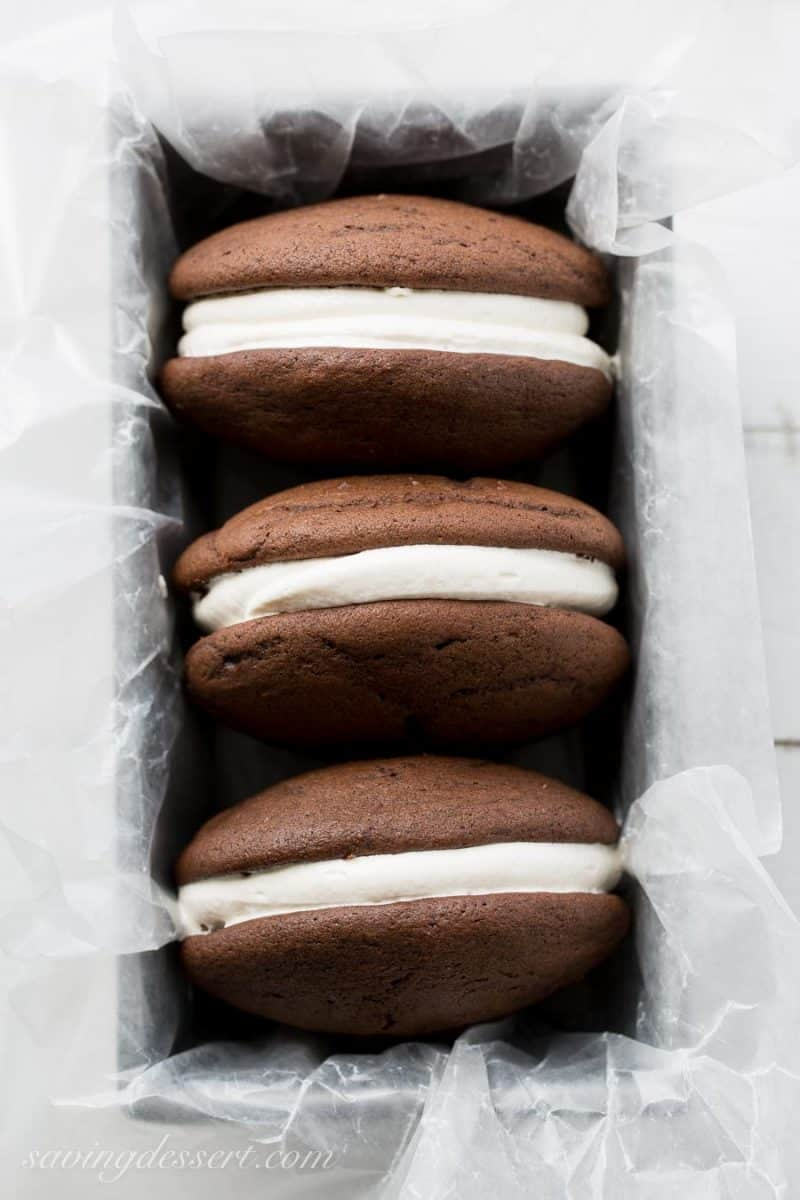 Classic Whoopie Pies ~ Chocolate cake-like batter is baked into large, soft hamburger-sized, bun shaped cookies then filled with a fluffy, sweet marshmallow frosting. www.savingdessert.com
