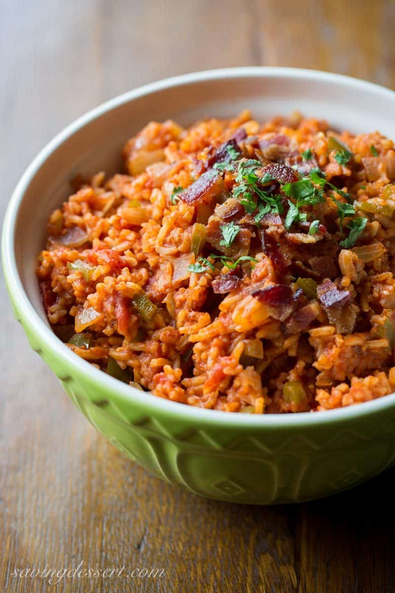 Spanish Rice in a bowl topped with crumbled bacon and parsley
