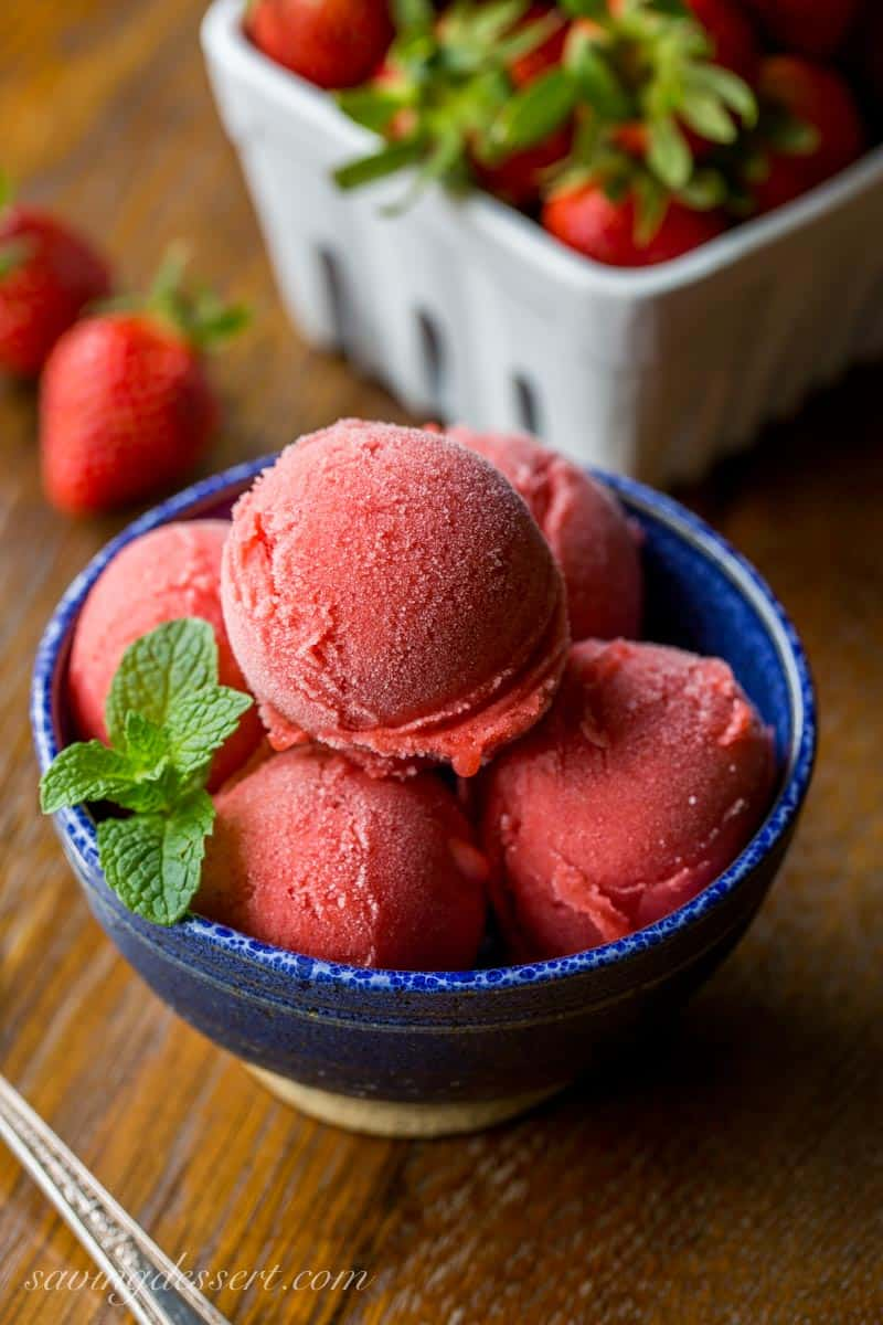 A bowl with scoops of strawberry sorbet garnished with mint leaves