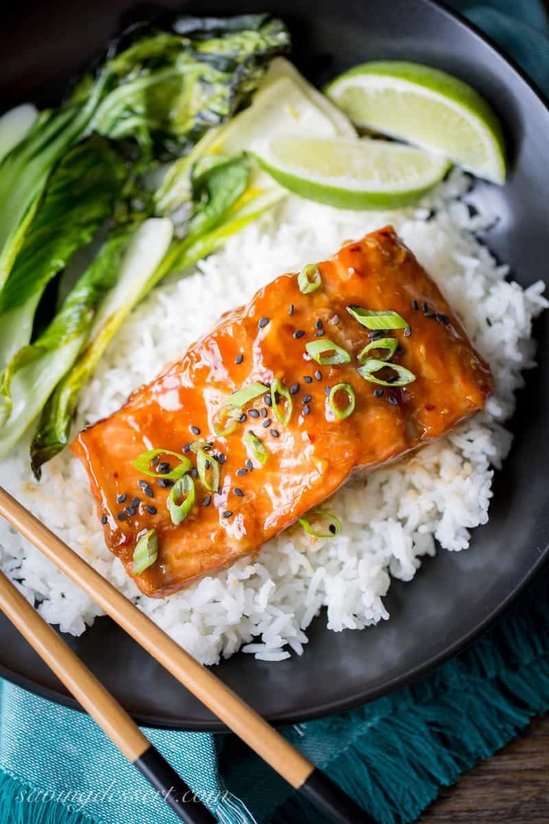 Teriyaki Salmon with green onions and black sesame seeds served on rice with lime and bok choy
