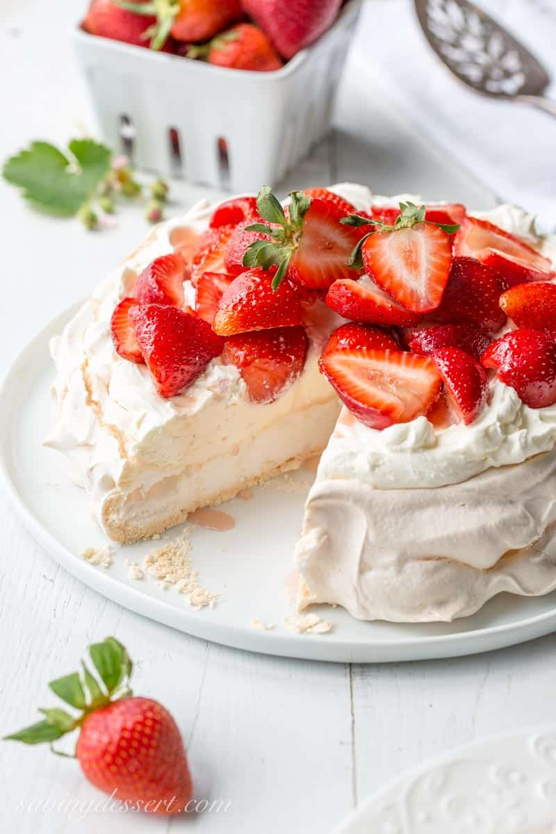 A sliced pavlova topped with mascarpone cream and fresh strawberries