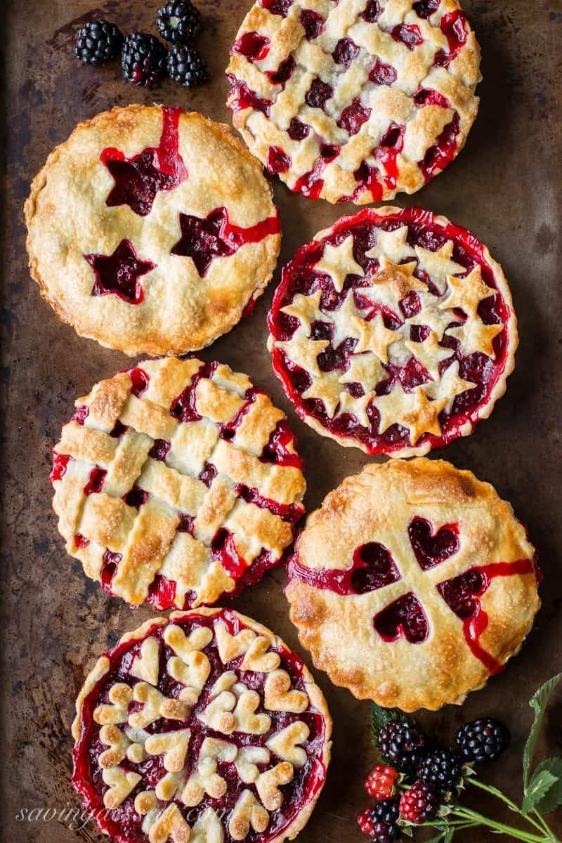 Six blackberry tarts with various designs