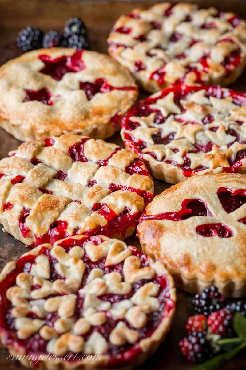 6 small blackberry tarts with flaky crust cut into different designs for each