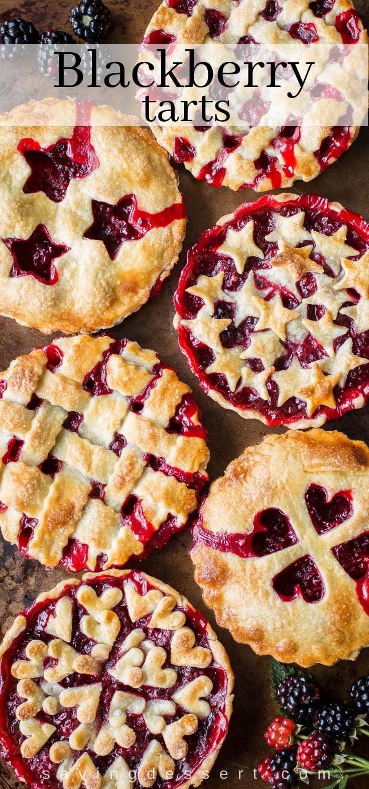 Six blackberry tarts with various designs on the top crust.