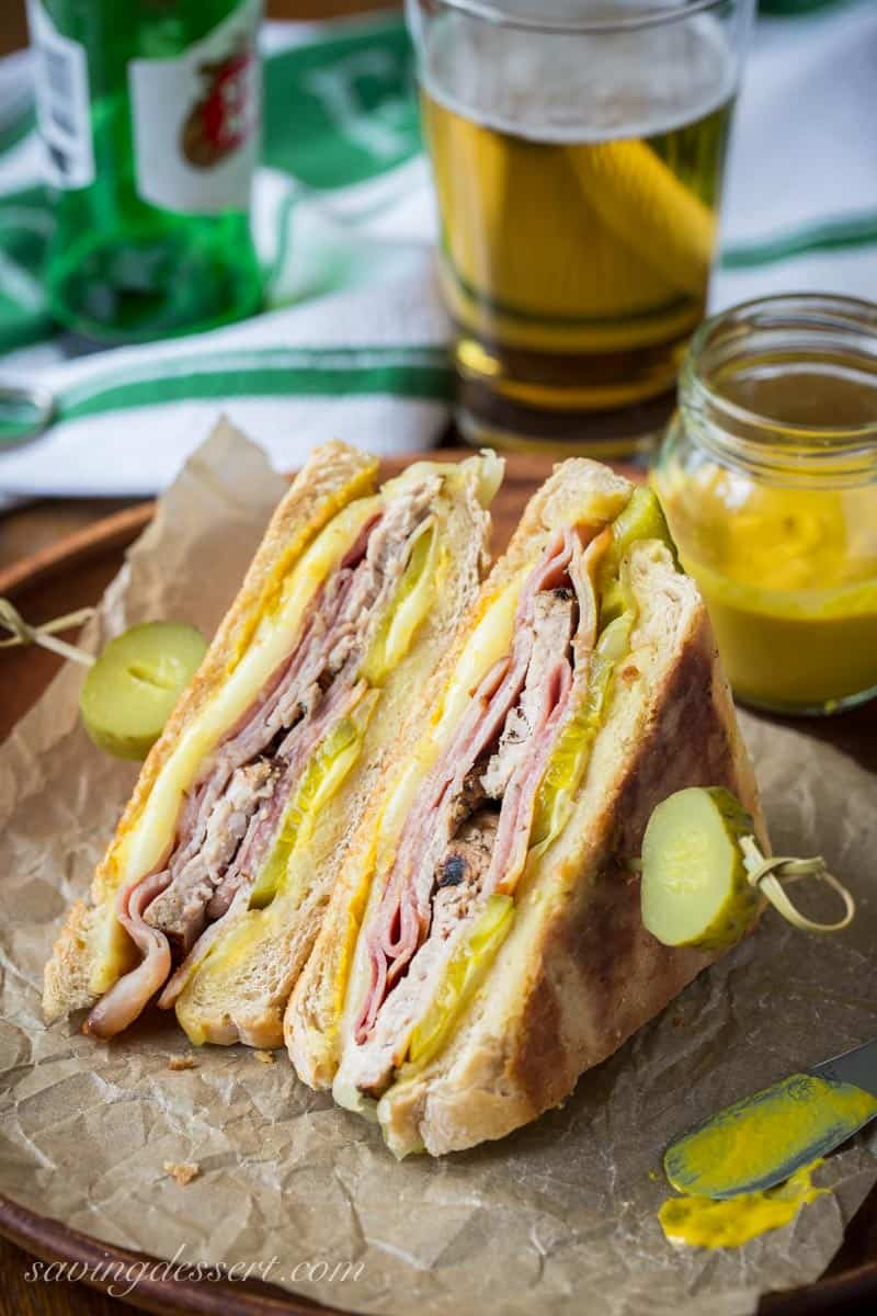 A cuban sandwich with pickles, sliced in half