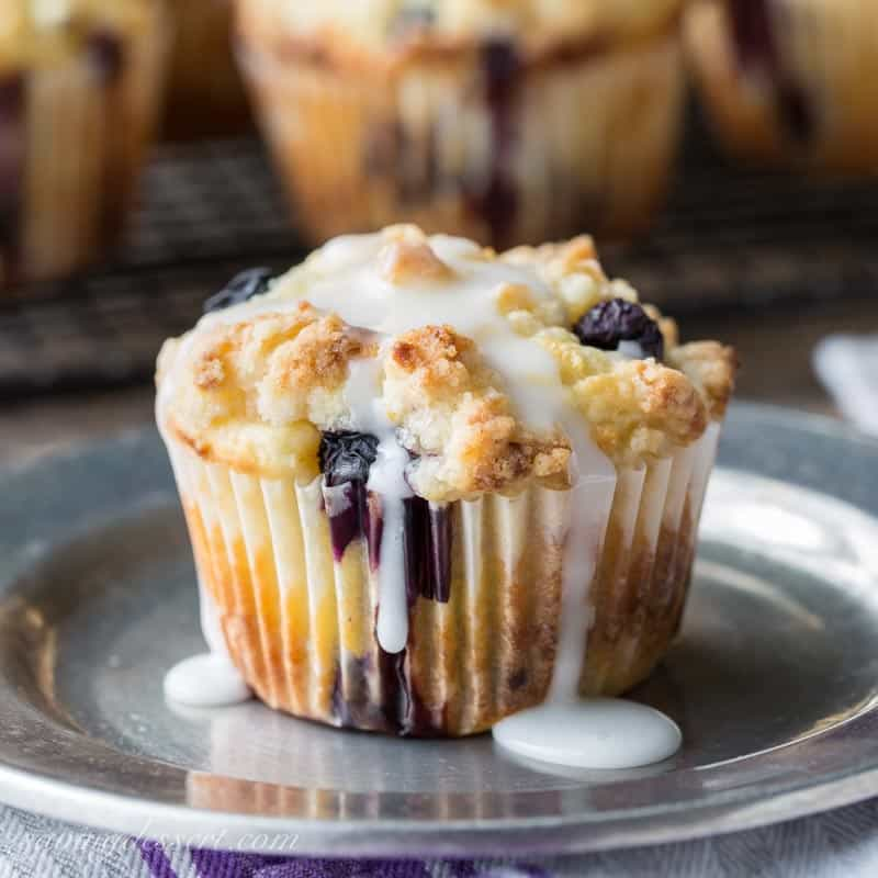 A crumble topped blueberry muffin with a lemon drizzled icing