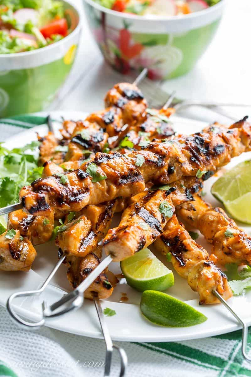 A plate filled with Grilled Chicken Skewers with a Sweet Sriracha Glaze, served with a salad and lime wedges