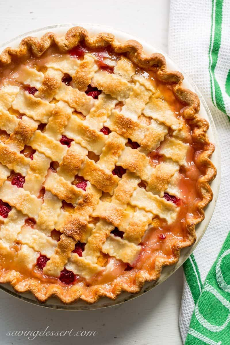 Peach Raspberry Pie with a Lattice Crust ~ juicy, sweet summer peaches are combined with tart raspberries for a wonderful seasonal dessert. Topped with a flaky, pretty, lattice weaved crust, this pie is a family favorite! www.savingdessert.com
