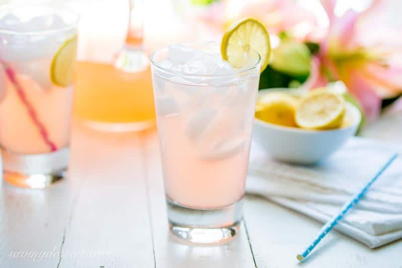 2 glasses of Pink Lemonade with a pitcher and fresh sliced lemons