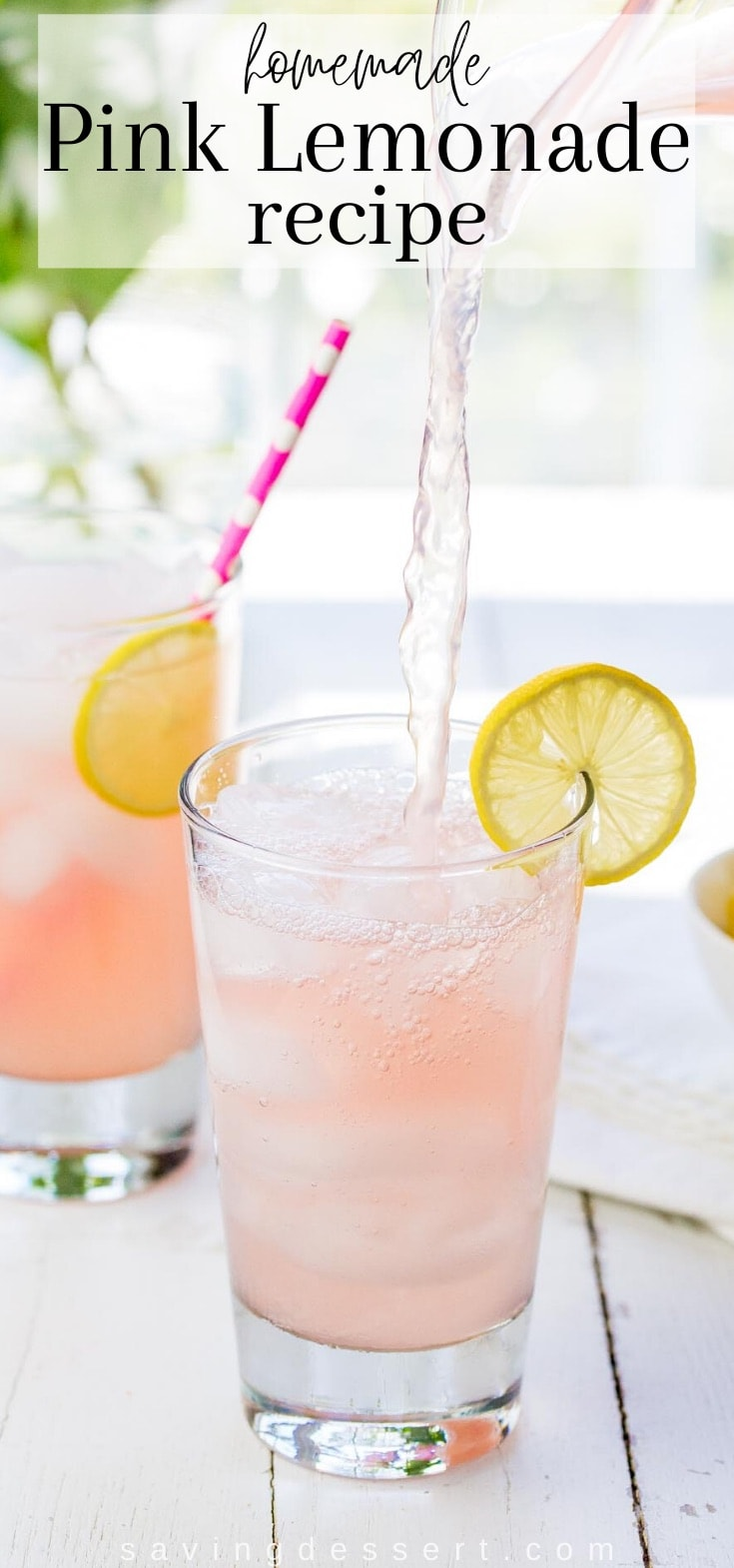 Two glasses of ice cold pink lemonade with lemon slices and a straw