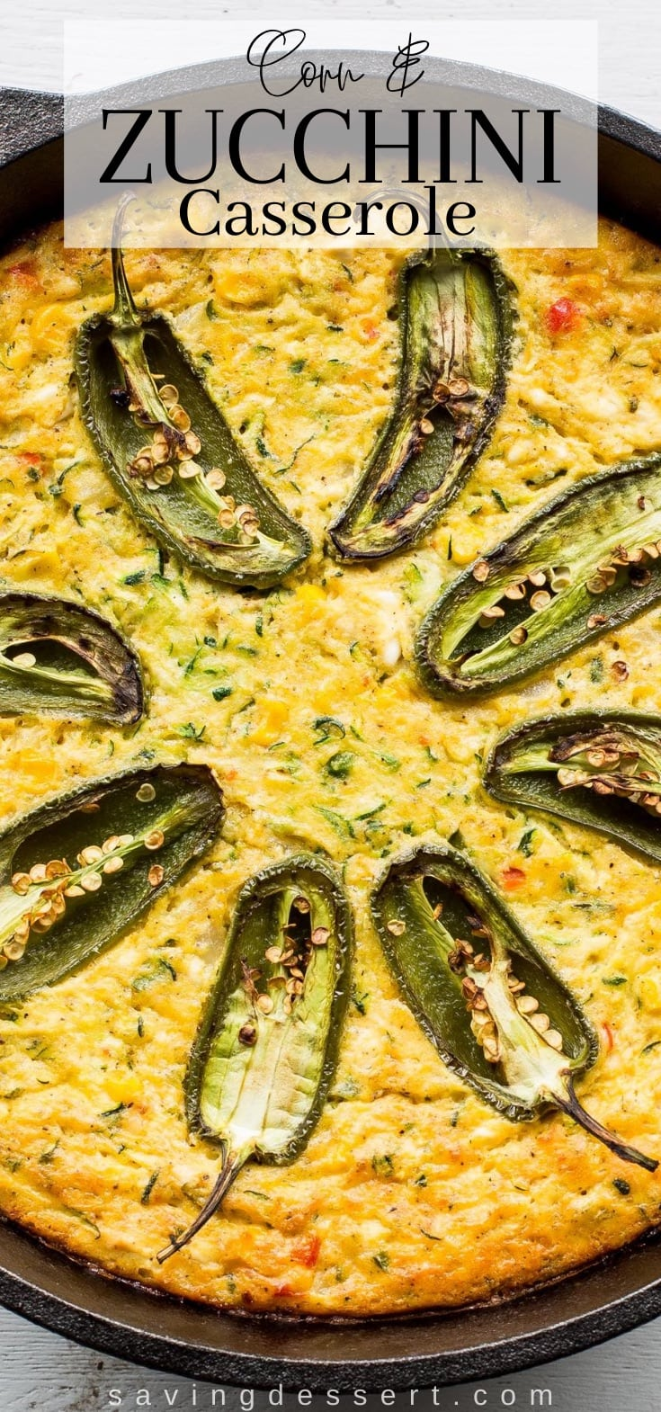 A cast iron pot filled with a corn and zucchini casserole topped with jalapeño peppers