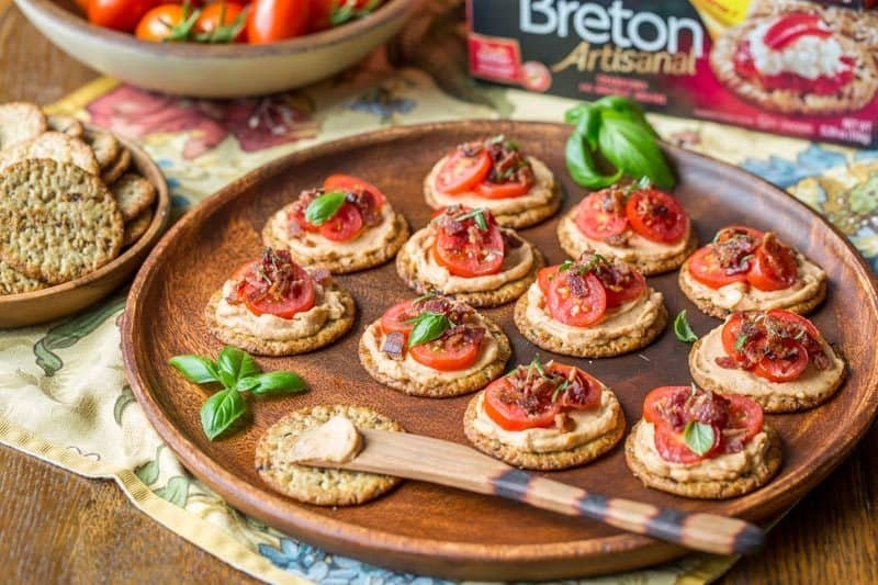 Mini BBQ BLT Appetizers - cream cheese blended with BBQ sauce then spread on our favorite Breton Artisanal Cranberry and Ancient Grains crackers. Topped with sliced cherry tomatoes and crumbled bacon, entertaining couldn't be easier! www.savingdessert.com