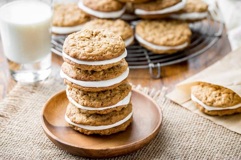 Oatmeal Cream Pies stacked on a wooden plate with a glass of milk
