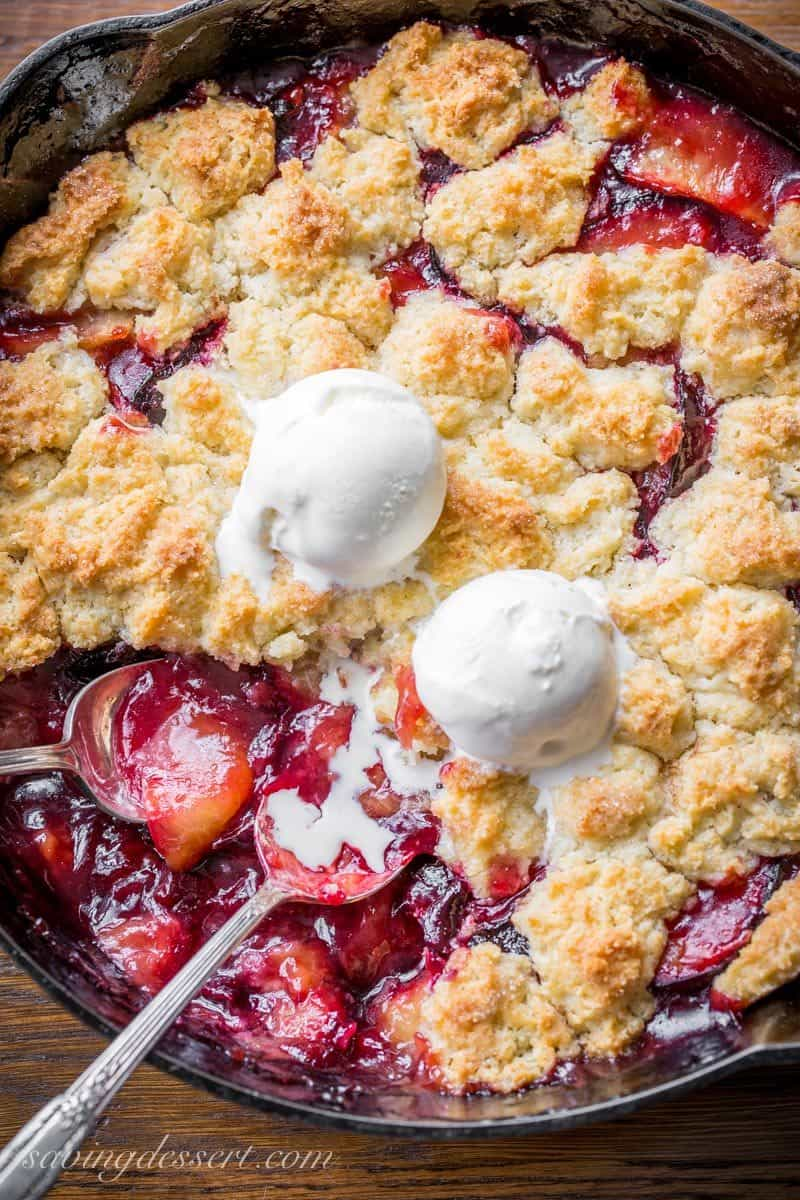 A cast iron skillet filled with a fruit dessert with a crumbled dough on top with scoops of ice cream