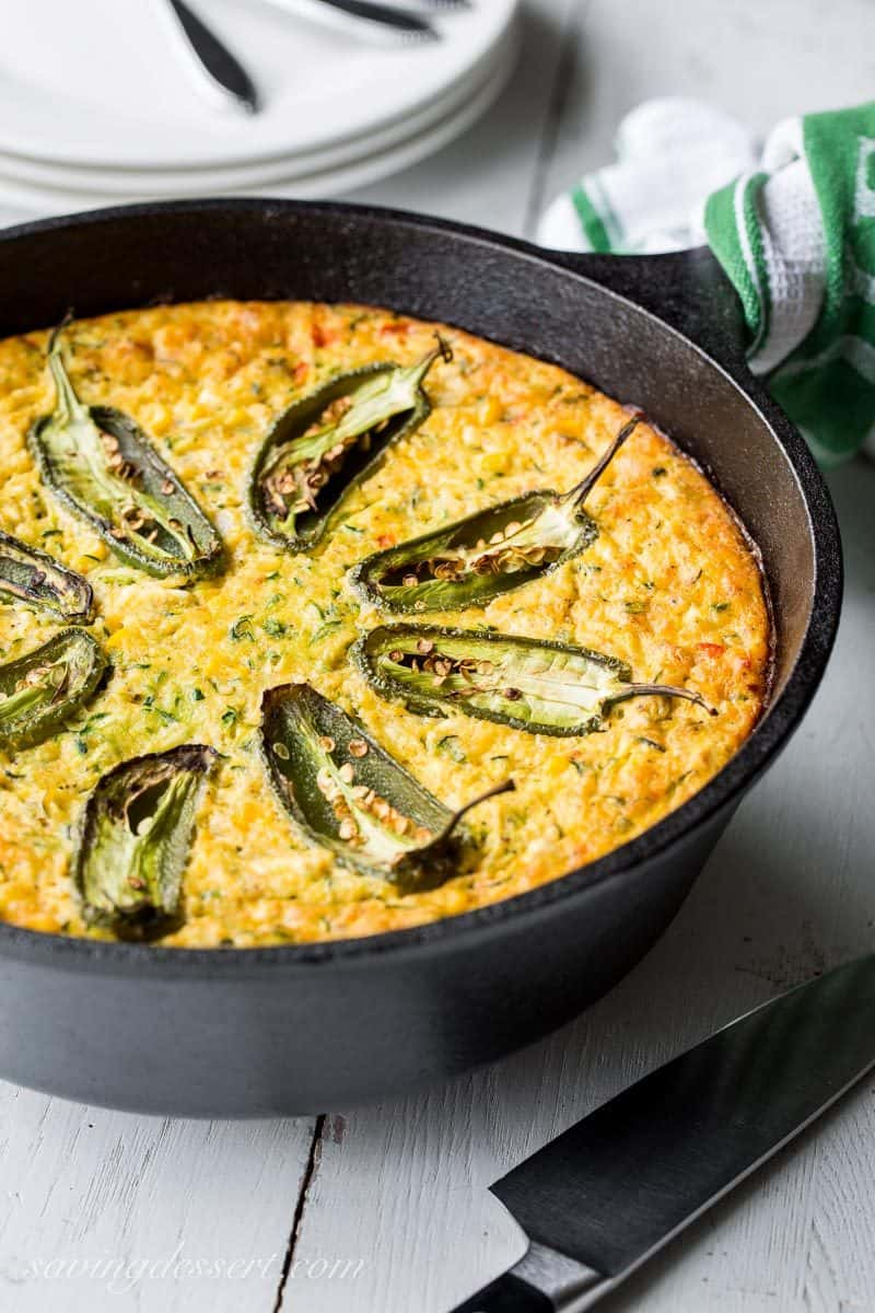 A cast iron skillet with a corn and zucchini casserole topped with jalapeños