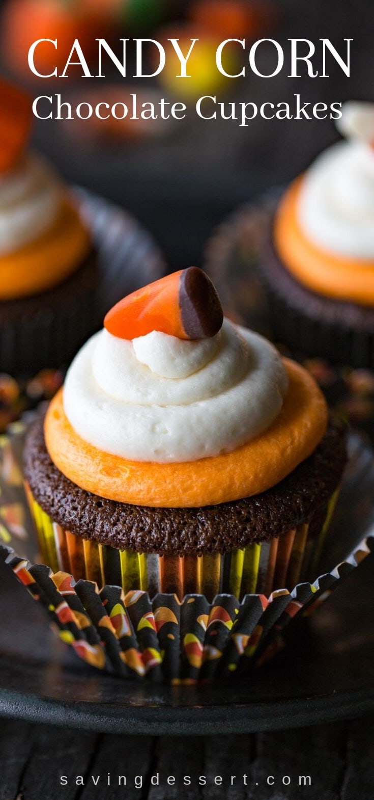 A chocolate cupcake topped with buttercream icing and a candy corn on top