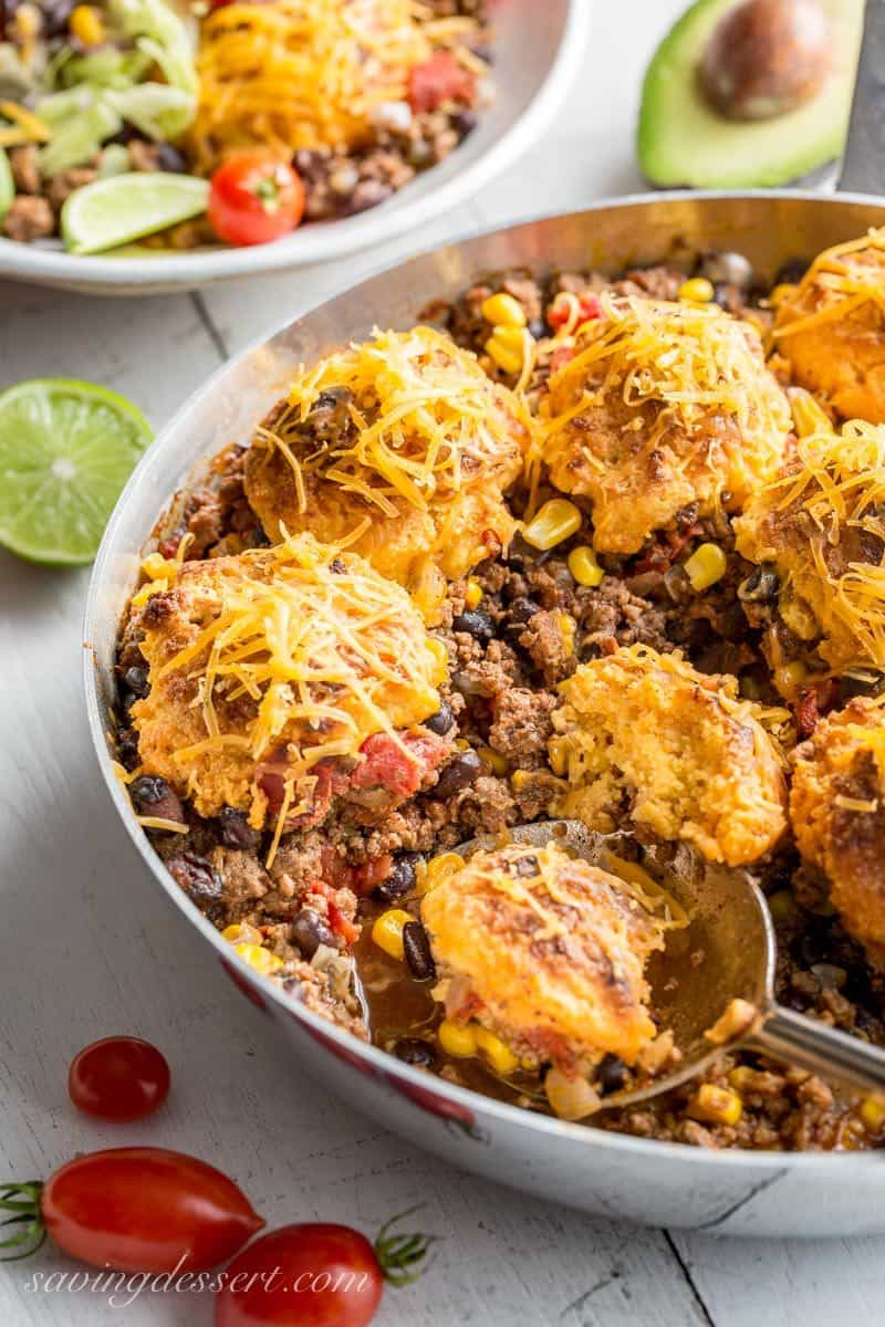 Skillet Taco Cobbler ~ ground beef, black beans, tomatoes and corn come together in a nicely spiced base for our tender, cheesy cornmeal biscuits. www.savingdessert.com #savingroomfordessert #cobbler #taco #tacocobbler #cornmealbiscuits