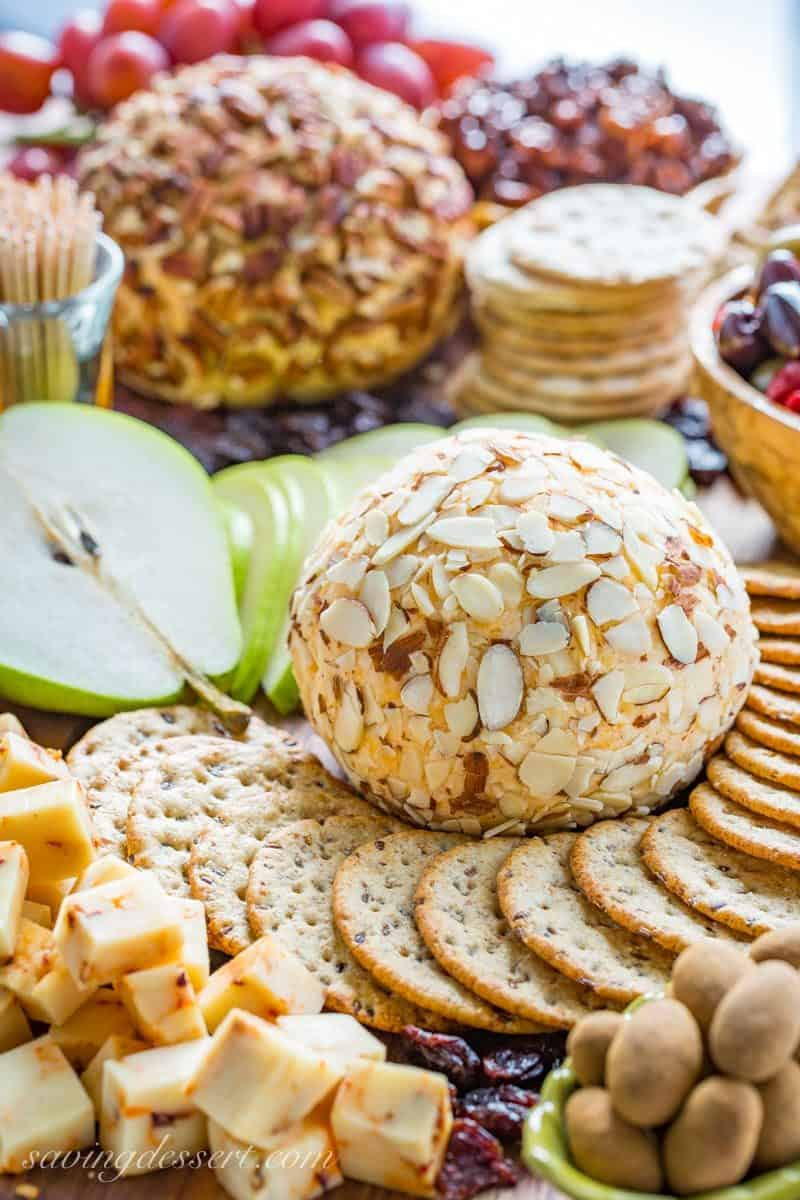 A party cheeseball covered in sliced almonds served with crackers, fruit, nuts and cheese