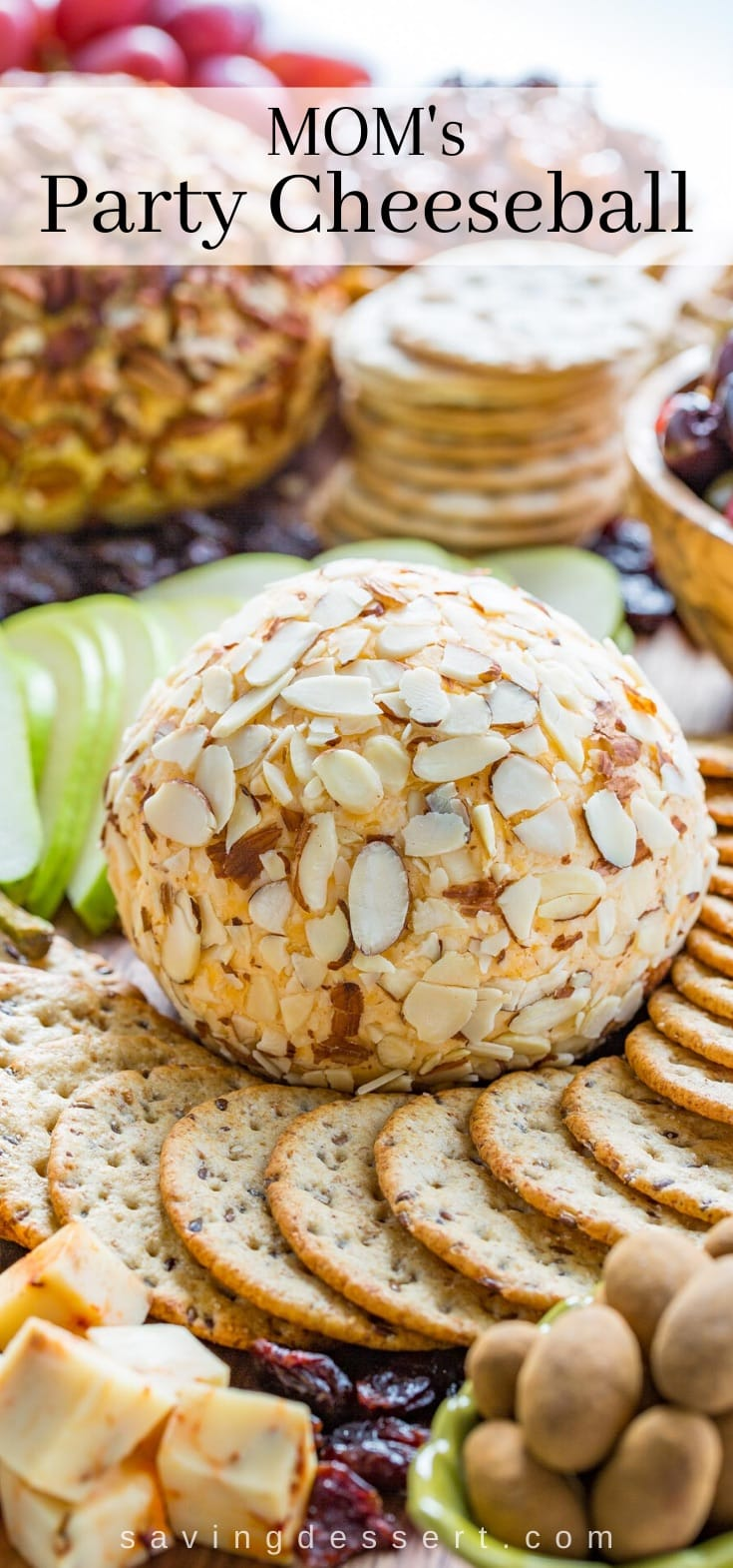 A cheeseball covered in sliced almonds on a platter of crackers, fruit, nuts and cheese