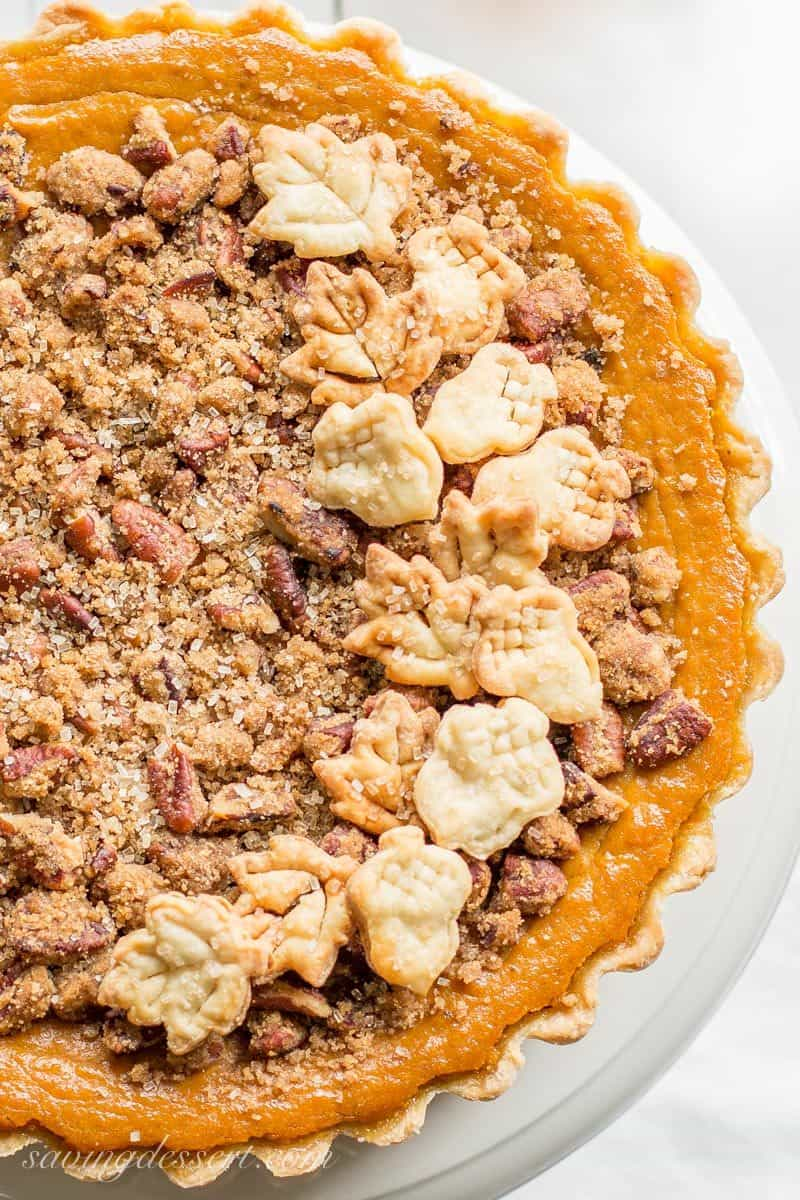 A pretty pumpkin tart with a pecan crumble on top and pastry cutouts to look like acorns and leaves