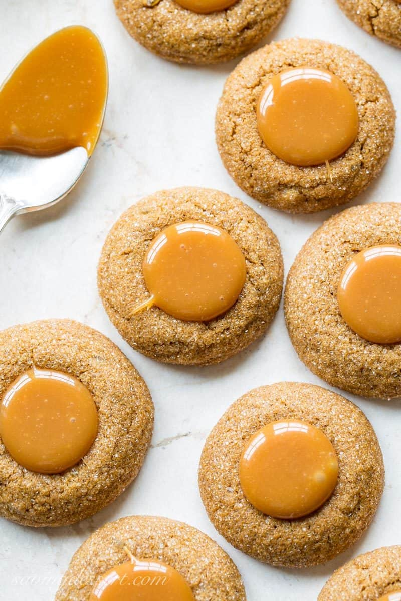Ginger Molasses Thumbprint Cookies with Caramel ~ a terrific little molasses cookie with a crisp exterior, plenty of bite from the ginger, and a smooth, gooey milky caramel center. www.savingdessert.com #savingroomfordessert #gingercookies #molassescookies #thumbprintcookies #thumbprint #christmascookies #cookies #caramelcookies