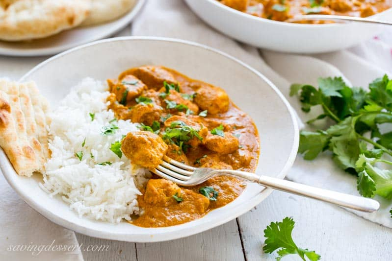 Indian Butter Chicken Recipe served with hot Basmati rice and naan bread, garnished with cilantro