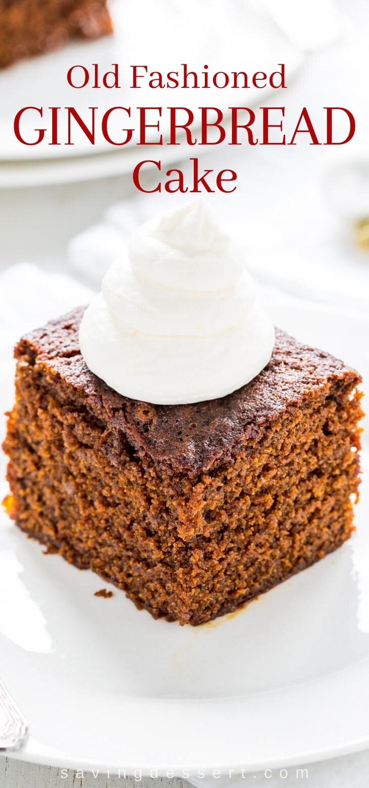 A slice of old fashioned gingerbread cake with lemon whipped cream on top