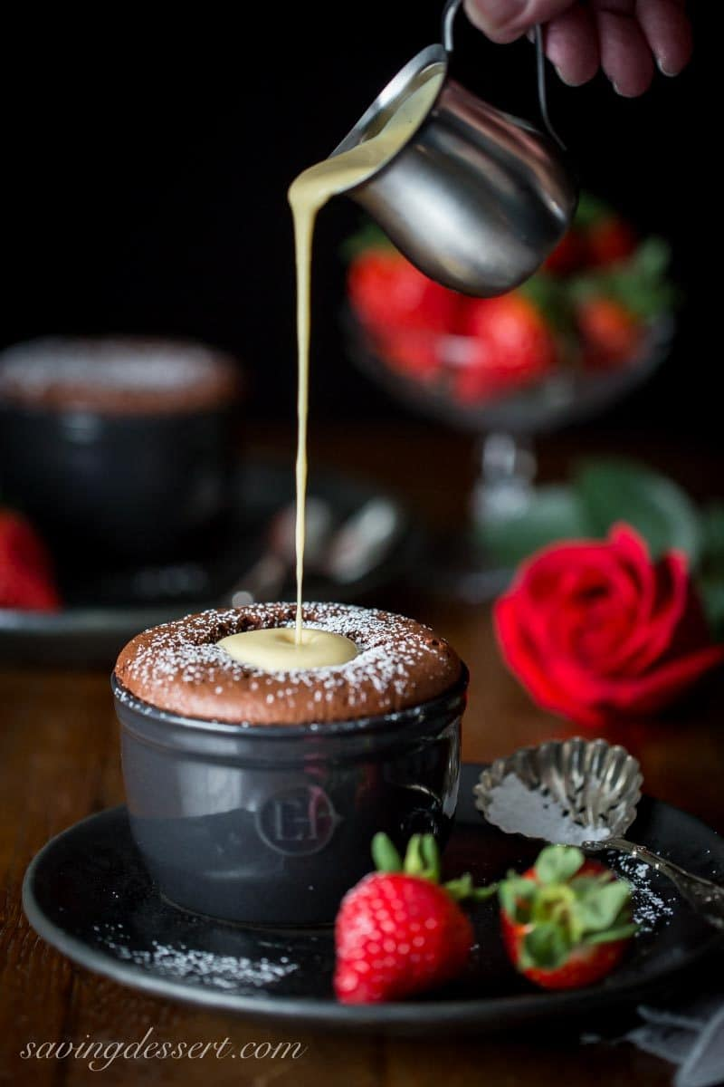 Pouring creme anglaise over an individual chocolate souffle with strawberries