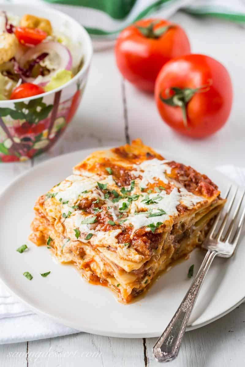 A big slice of meaty, cheesy homemade lasagna with fresh tomatoes and salad on the side from www.savingdessert.com