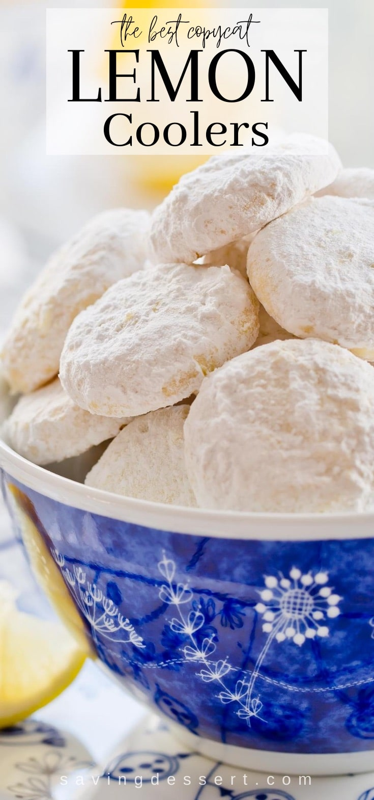 A blue bowl filled with powder sugar covered lemon cookies