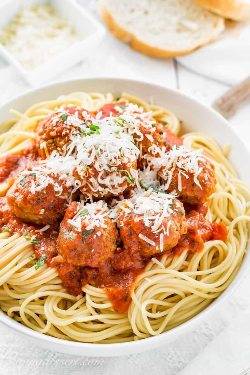 A bowl of spaghetti topped with Italian Style Meatballs and plenty of grated Parmesan cheese