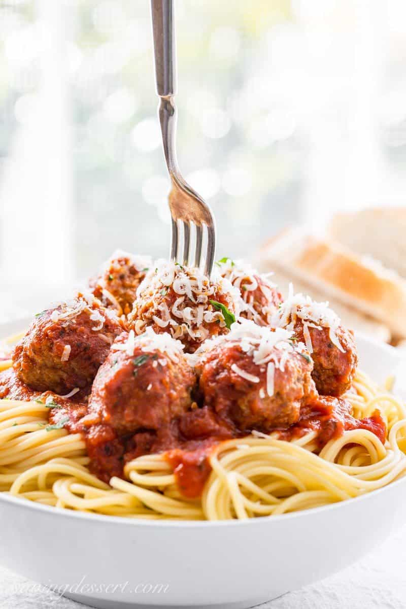 Bowl of spaghetti with meatballs and shredded Parmesan Cheese with a fork