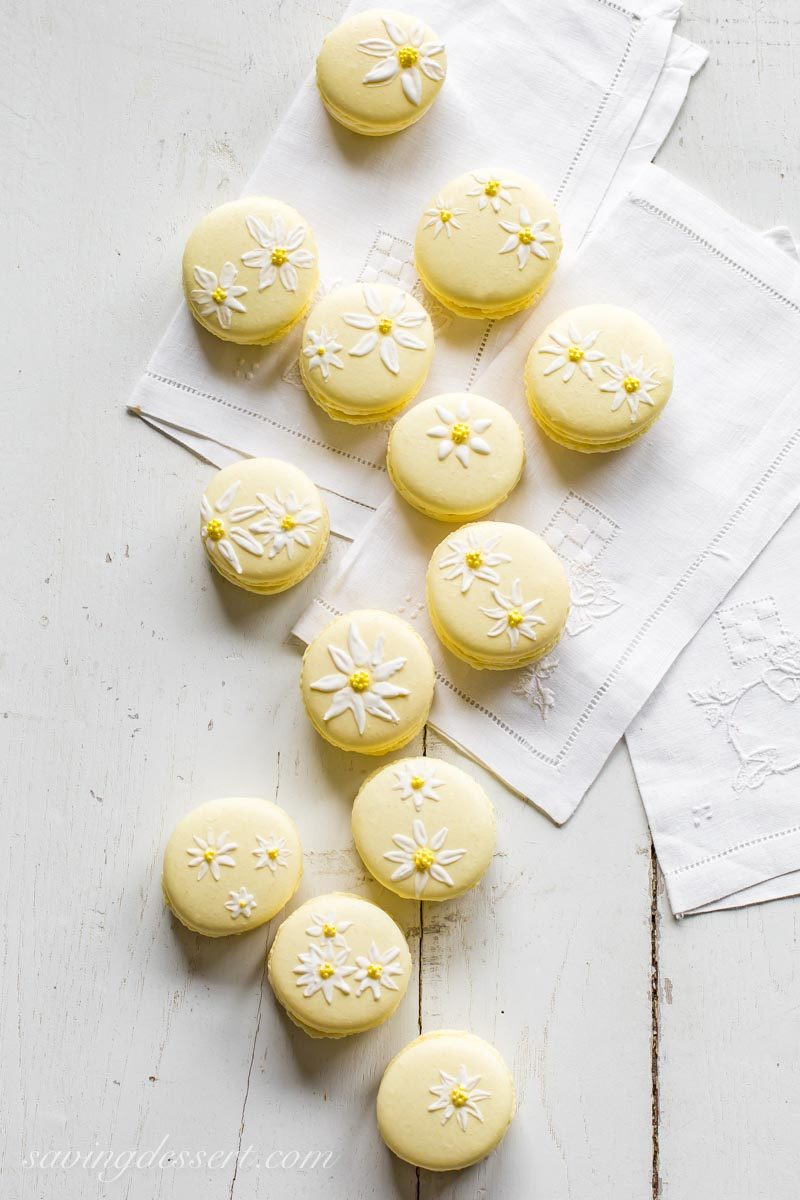 Pretty yellow macaron cookies painted with daisies using royal icing