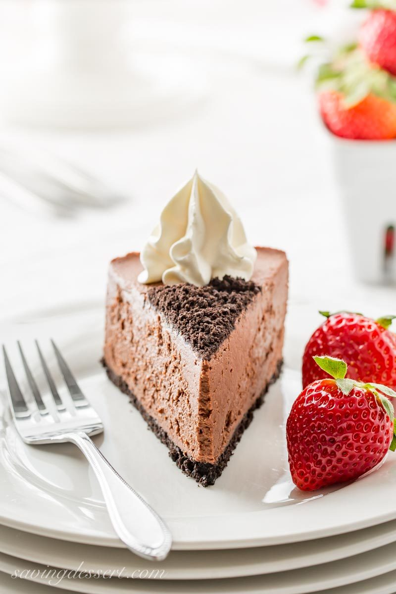 a slice of baileys chocolate cheesecake with whipped cream and strawberries