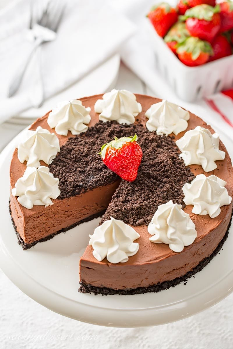 A sliced no-bake chocolate cheesecake topped with cookie crumbs, whipped cream and strawberries
