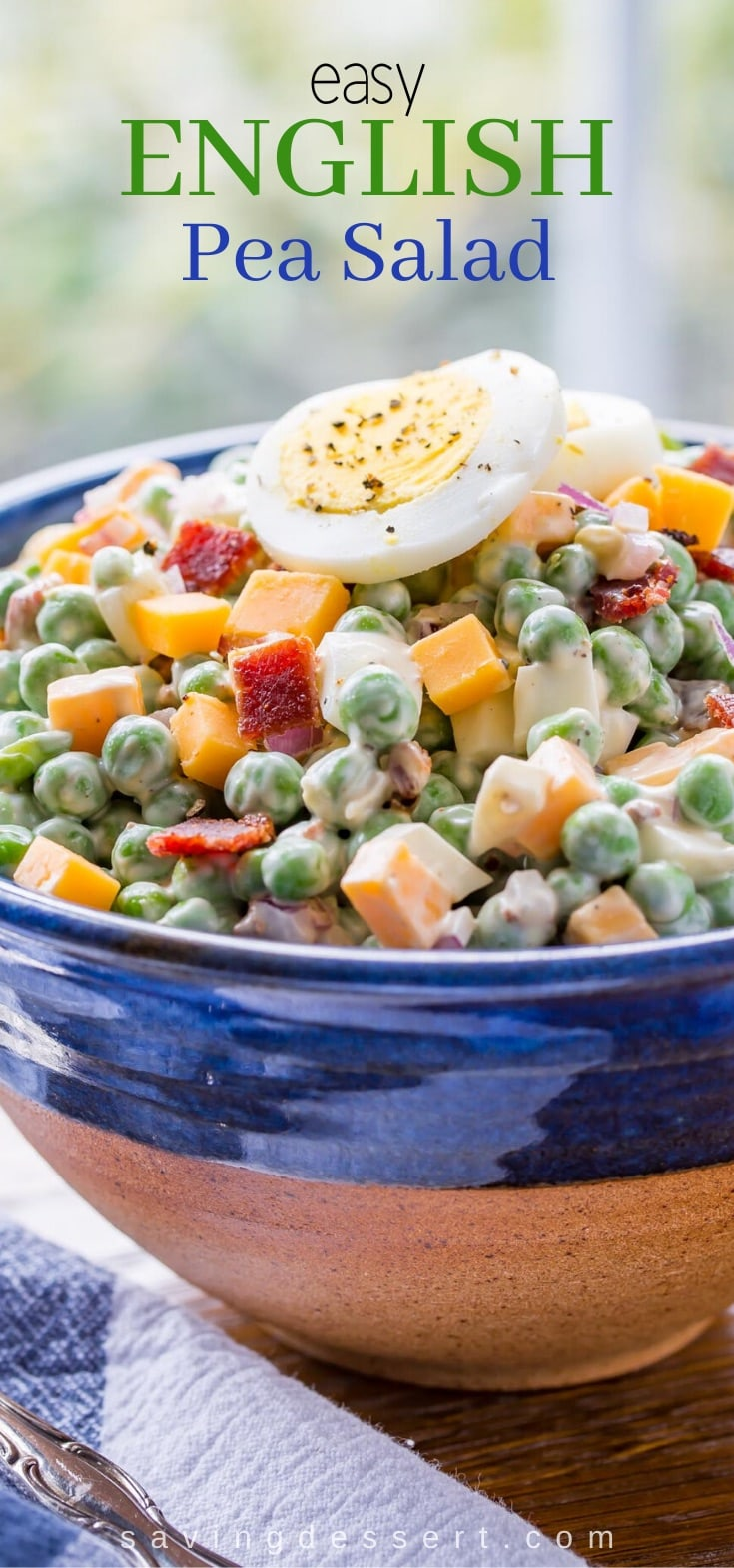 A bowl of pea salad with cheese, bacon and topped with a hard cooked egg