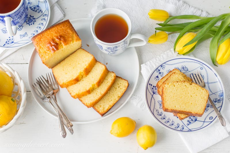 lemon ricotta pound cake sliced, with lemons, tea and yellow tulips