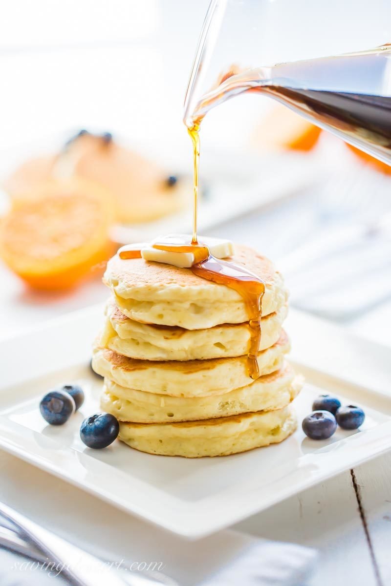 maple syrup being poured over a stack of ricotta pancakes