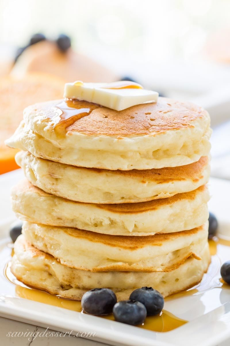 ricotta pancakes with syrup, blueberries and a pat of butter