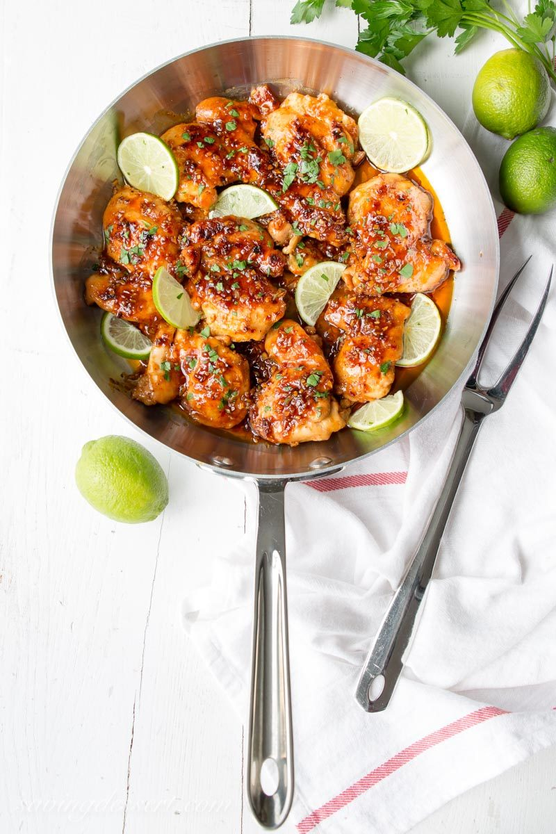 Skillet with chicken thighs coated in a garlic, lime, honey sauce garnished with lime wedges