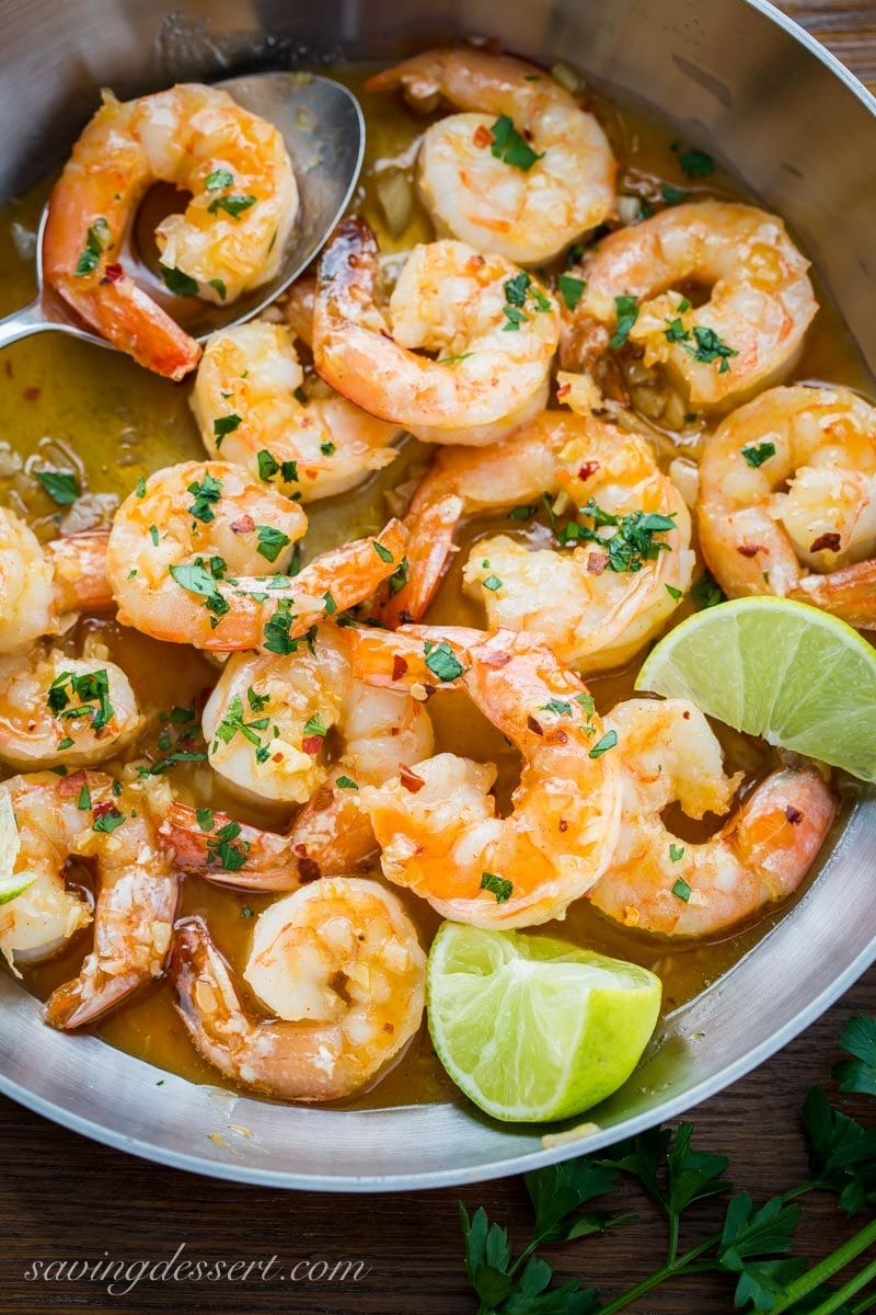 skillet with spicy shrimp in a honey lime sauce with fresh lime wedges and parsley
