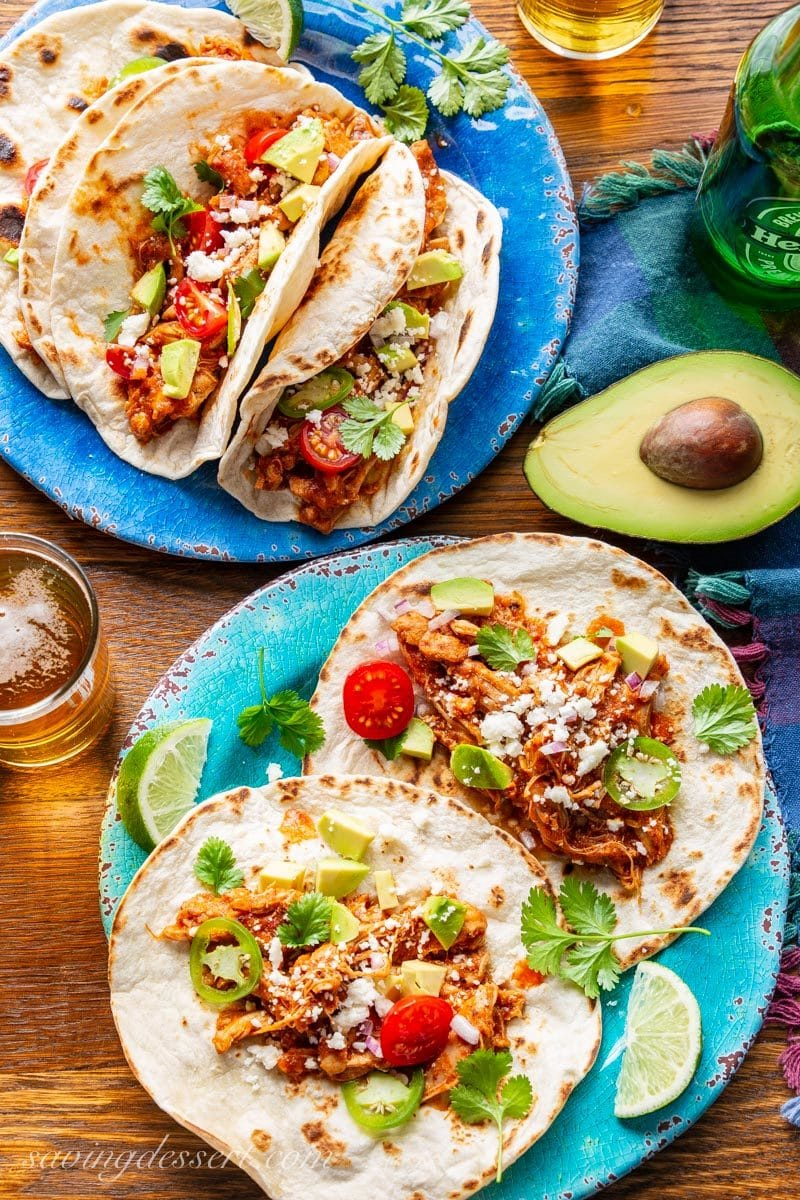 Plates with Chicken Tinga Tacos topped with avocado, tomatoes and cheese