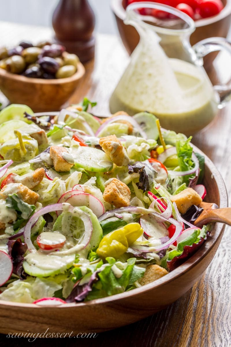 A wooden salad bowl filled with lettuce, radishes, peppers and onions drizzled with creamy Italian dressing.